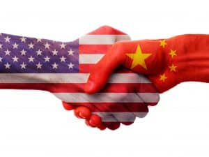 USA and China bilateral political relations and cooperation concept with American flag and Chinese flag painted on handshake.